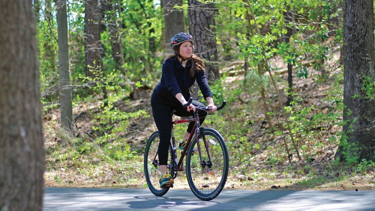 Student riding bike on Raleigh greenway system.