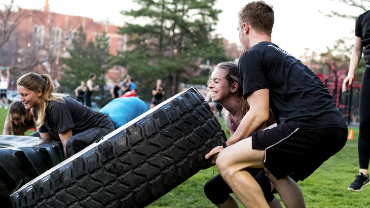 NC State students working together to flip a tire on Miller Fields