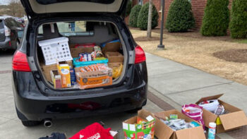 Back of a car with boxes of donated supplies in the truck and on the ground.