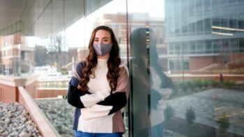 Victoria Moore poses in front of the WellRec Center while wearing a face covering