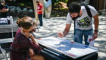 A male student marks his hometown on a map of the world as a female student looks on.